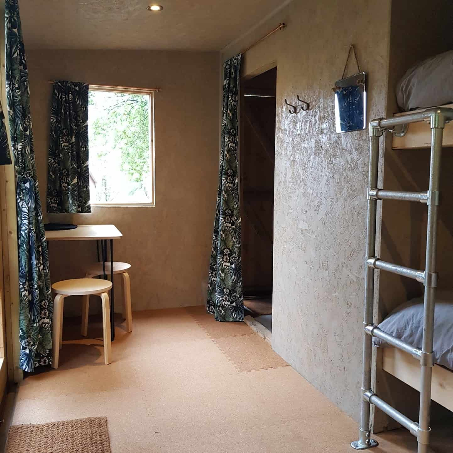 Cabin living area with table and four stools and a storage area for bikes, gear etc