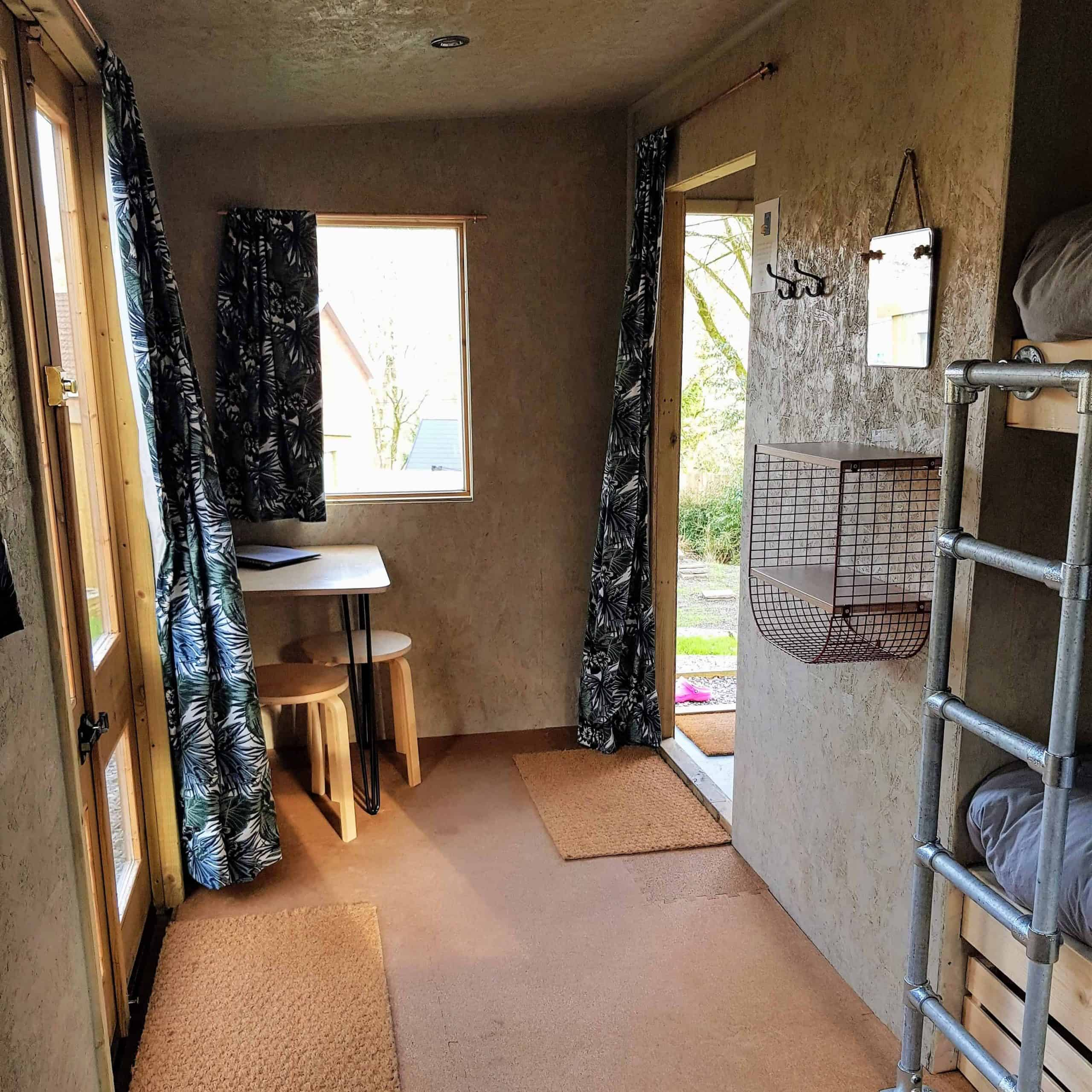 Glamping cabin with table, stools, storage and curtains