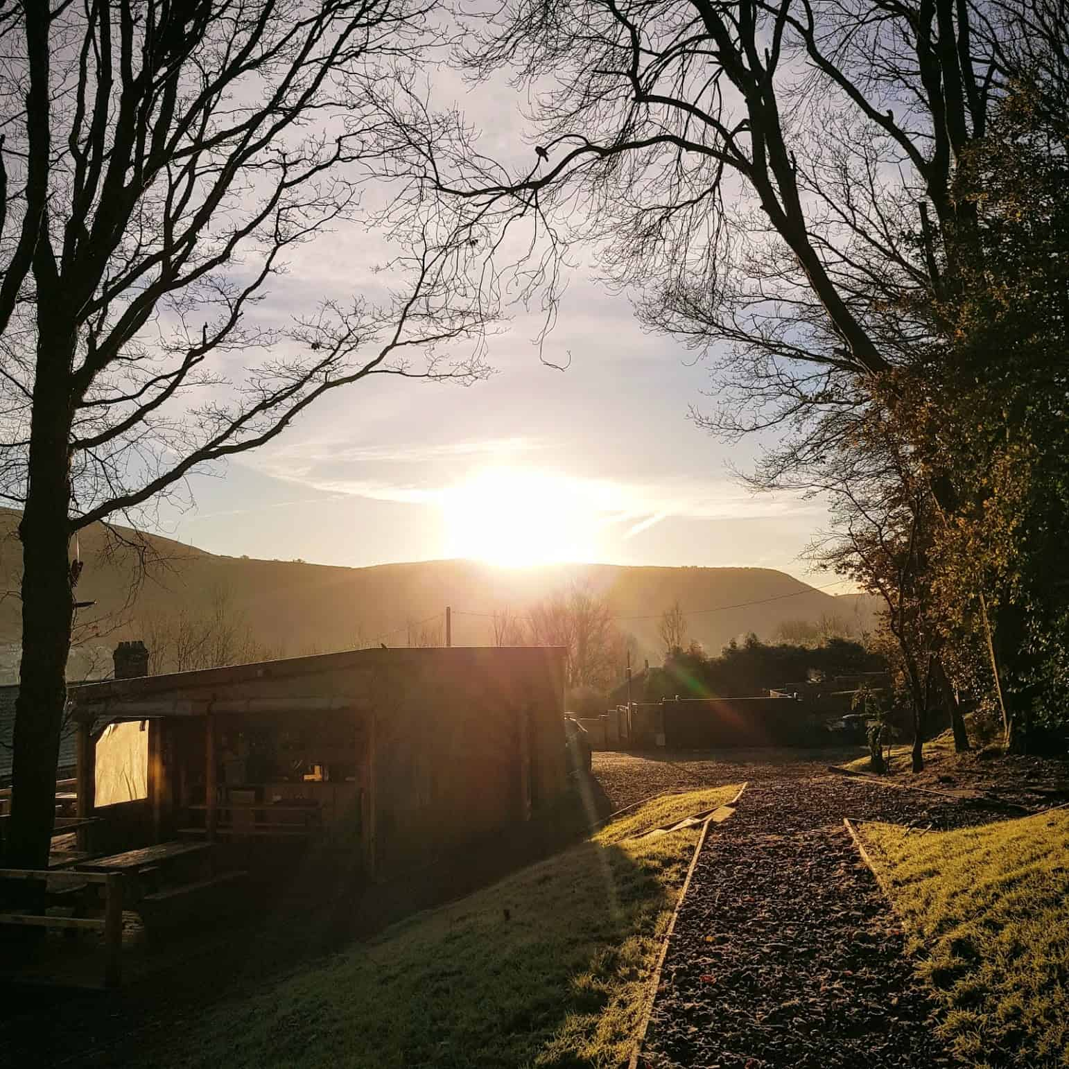 The sun rising over the roost cabins