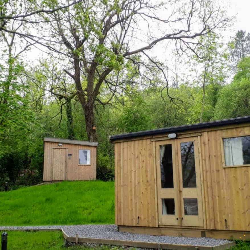 Glamping cabins Bodlawen and Noddfa with a back drop of trees