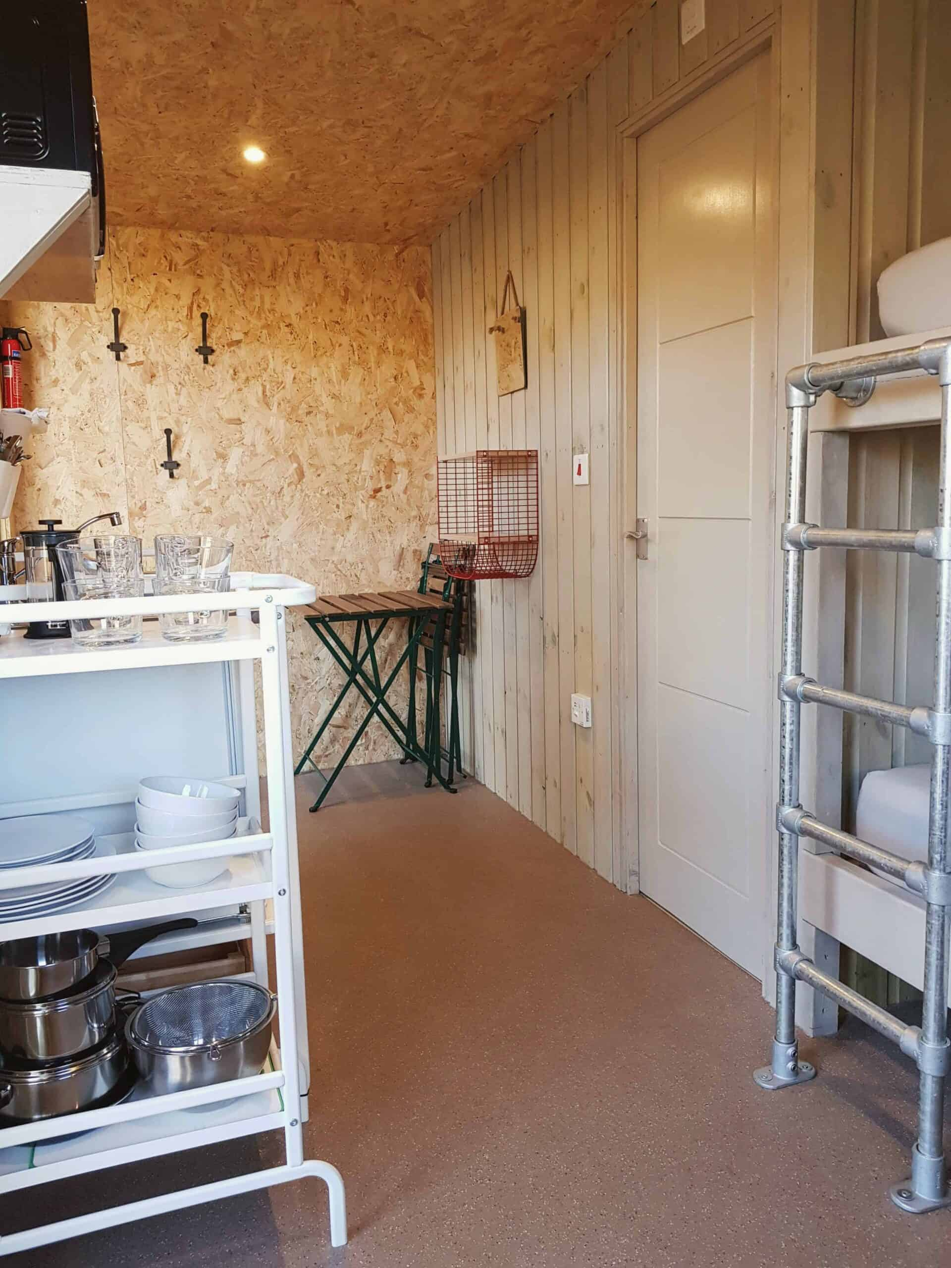 Cabin layout with hooks, table, kitchenette, bunk bed ladder, door to ensuite