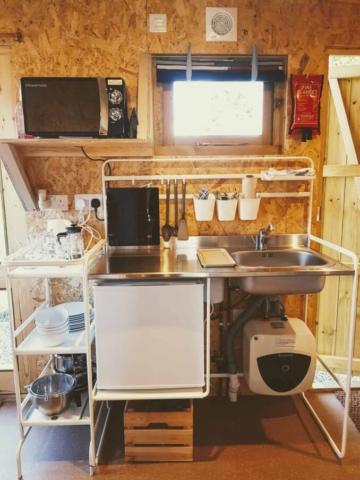 Cabin kitchenette with microwave, sink, hob, fridge, water heater, pots, pans, crockery