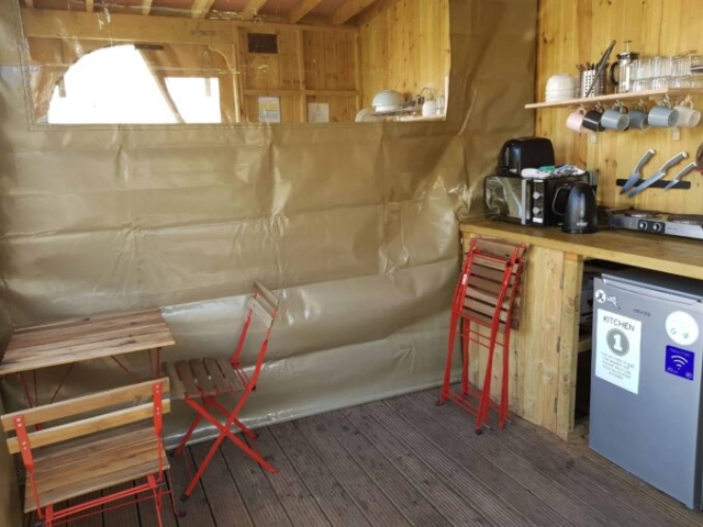 Well kitted out camping kitchen with crockery, utensils, microwave, fridge, kettle, toaster, sink.