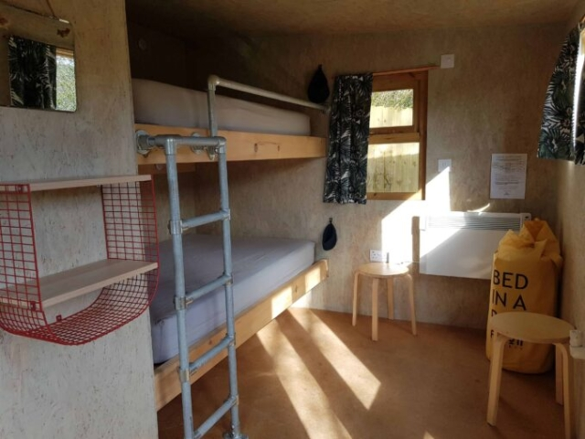 Cabin interior with big bunk beds stools and heaters